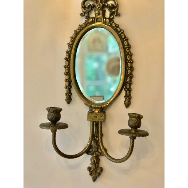 Neoclassical Italian vintage mirrored wall sconce with a brass cast urn over a beautifully aged oval beveled mirror...