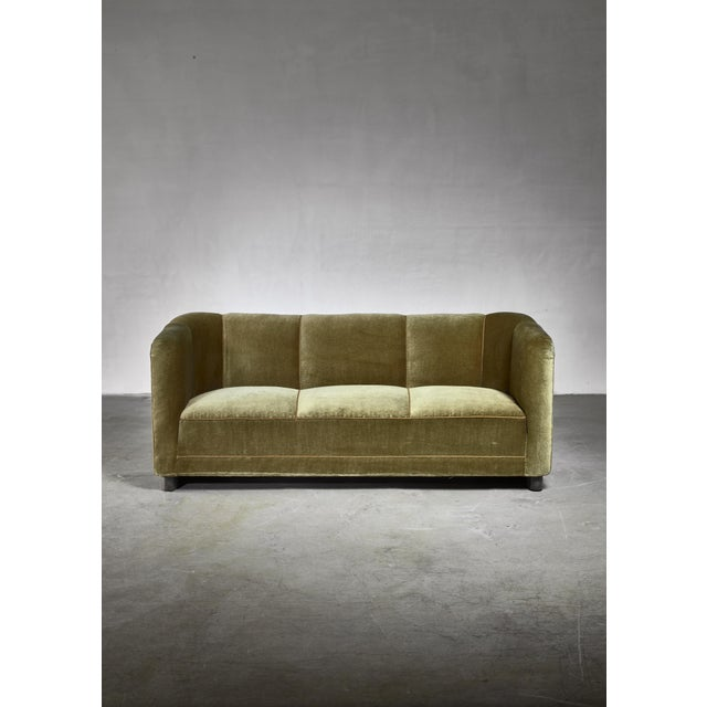 A model 1668 sofa designed by Ole Wanscher for Fritz Hansen with green velour upholstery. The sofa has the combined beauty...