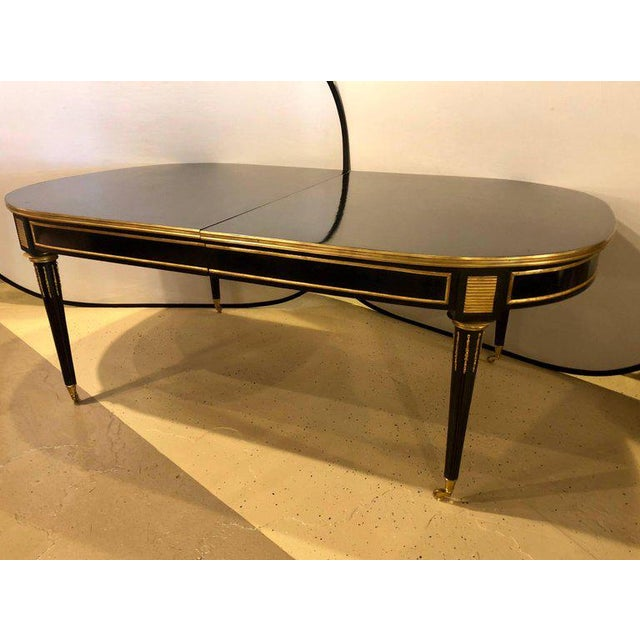 An Ebonized Maison Jansen Style Twelve Foot Dining Table in Louis XVI Fashion. This finely constructed strong and study...