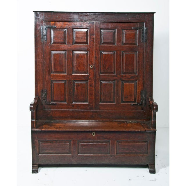 English early 18th century oak Bacon Settle c. 1720 of superb color and condition. The field paneled doors open to reveal...