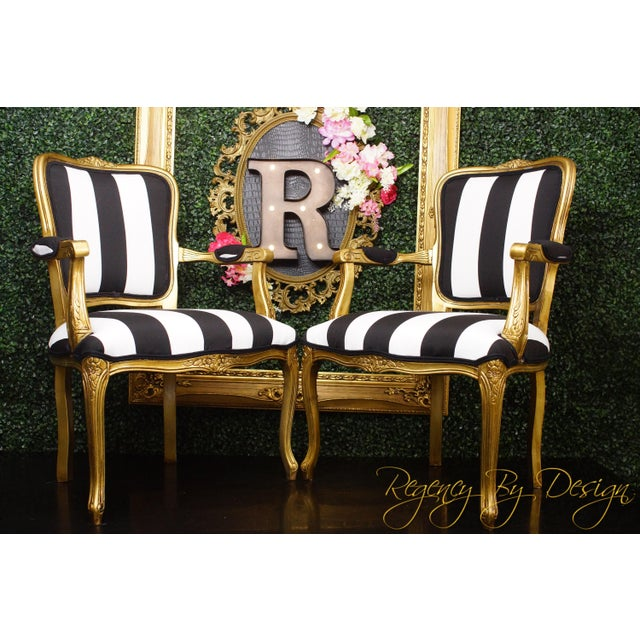 A pair of newly upholstered vintage Louis XV style chairs, done in a chic black and white upholstery fabric, with a...