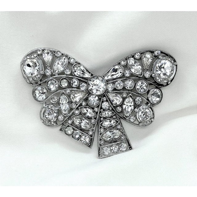 Beautifully designed c.1930s to 1940s rhodium-plated brooch in a stylized bow design, set with round, pear-shape and...