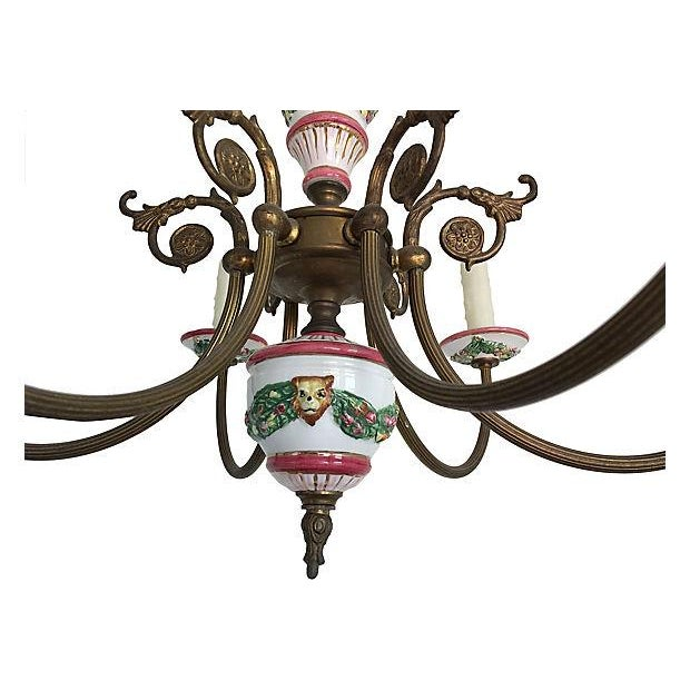1940s French six-arm chandelier featuring hand-painted porcelain lion's heads and floral garlands with scrolled and fluted...