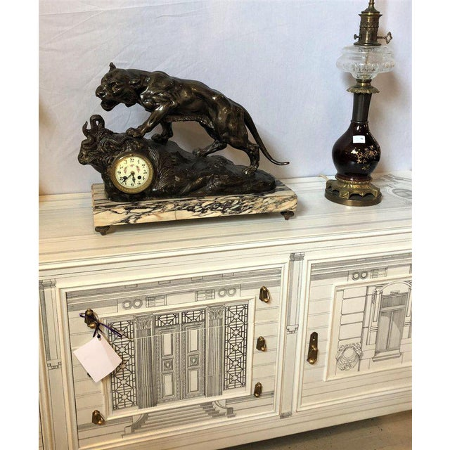 A zinc tiger challenging a rattlesnake on a marble base having a mantle clock on the metal mountain. The works signed and...