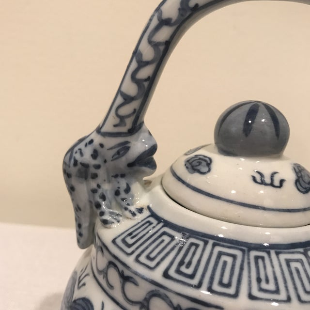 Lovely blue and white teapot with whimsical handles.