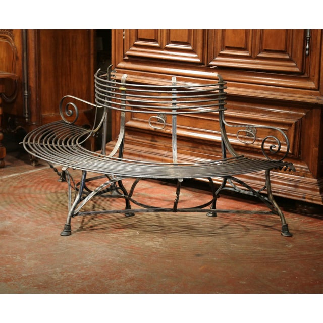 This elegant, curved iron bench was created in France. This durable bench is shaped so that it could wraparound a tree,...