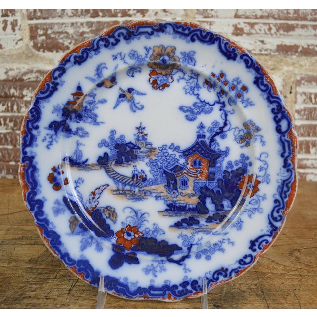 A set of 12 English 19th century ironstone flow blue transferware Chinoiserie plates in the style of Blue Willow with a...