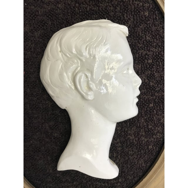 This is a beautiful framed ceramic/porcelain portrait of a young boy's profile. I just adore the gold color on the oval...