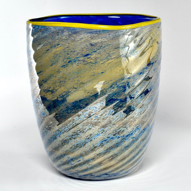 Large art glass vase has a saturated cobalt interior with yellow lip and striated blue and gold outer surface. Dates from...