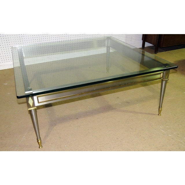 John Vesey style glass top coffee table with a chrome base and brass accents. This piece would look great in a mid-...