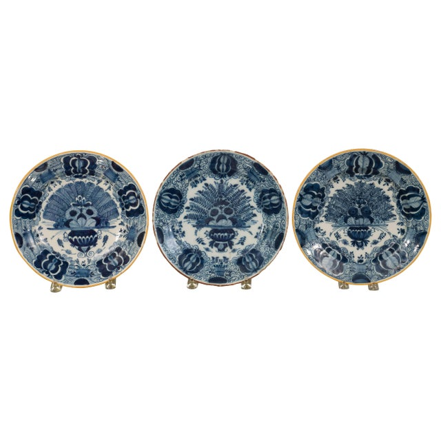 A series of three Dutch delft blue and white chargers hand-painted in a stunning deep blue with a yellow rim. The hand-...