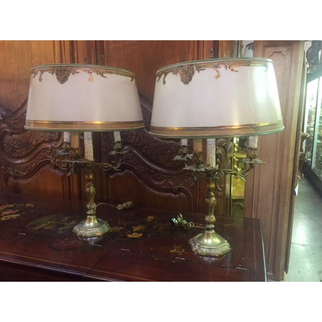 Pair of 1900s French bronze candle lamps. The pieces feature 3 arms each, and the shades are included.
