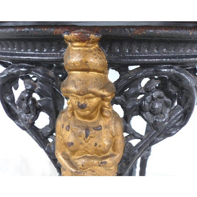 Offered for sale is a late 19th century cast iron table with cabriole legs topped by a bust of Britannia with lion paw...