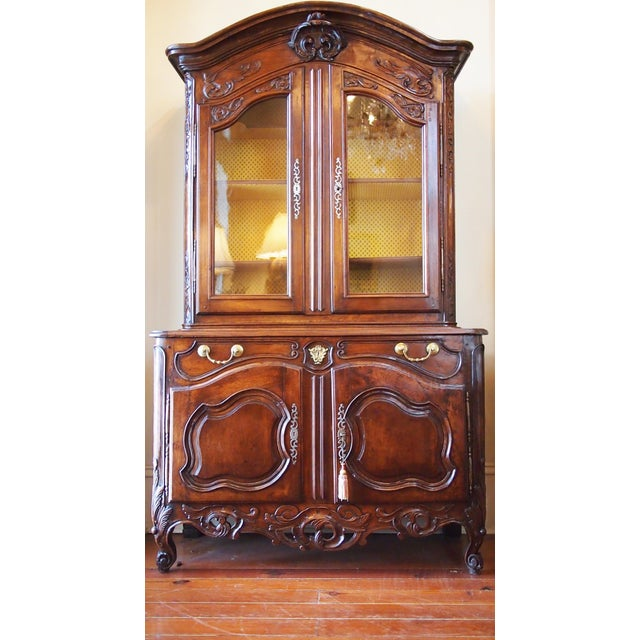 A beautifully scaled 18c French walnut two-piece cabinet, the stepped back top with an arched and deeply molded cornice,...