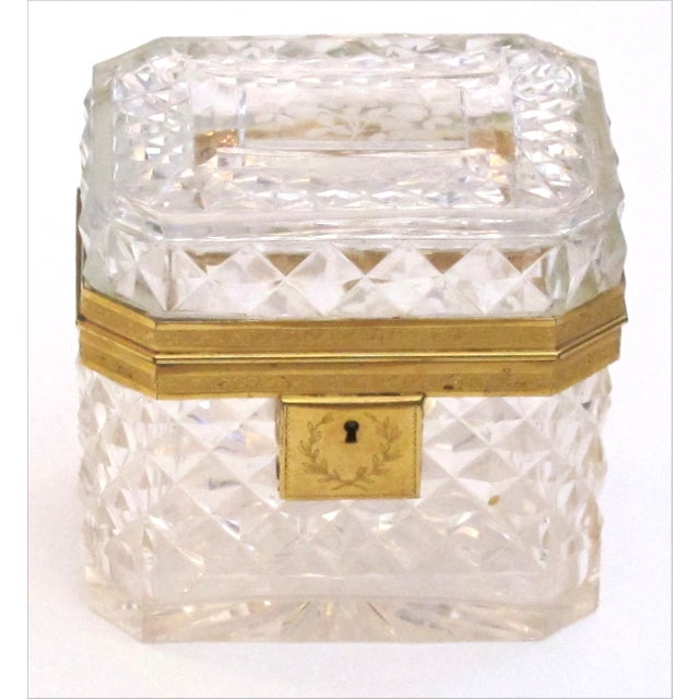 of rectangular shape with canted corners this crystal trinket box with a hinged lid; adorned overall with finely chased...