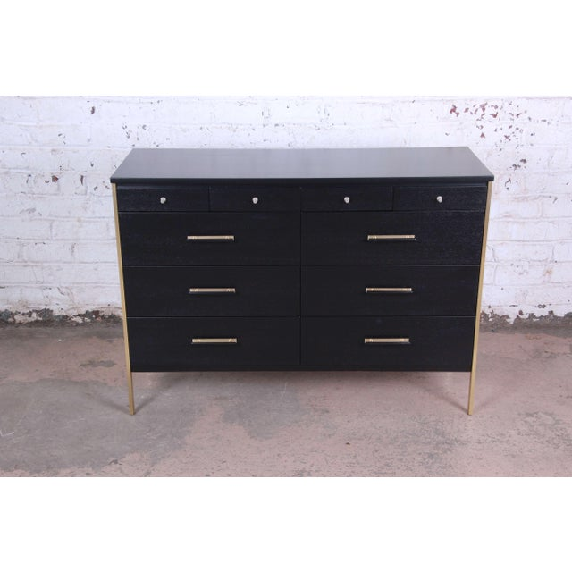 Offering a stunning ebonized Paul McCobb for Calvin Furniture ten drawer dresser. The dresser distinguished brass legs and...