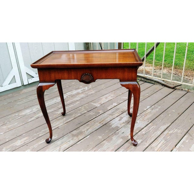 Item offered is a Brandt mahogany table with 2 pullouts. One on each end of the table. The table has a raised rim with...
