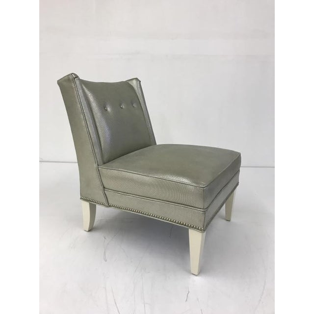The Foxx Armless Chair is a first quality market sample that features a Green Fabric with a Cream Finish and a Brushed...