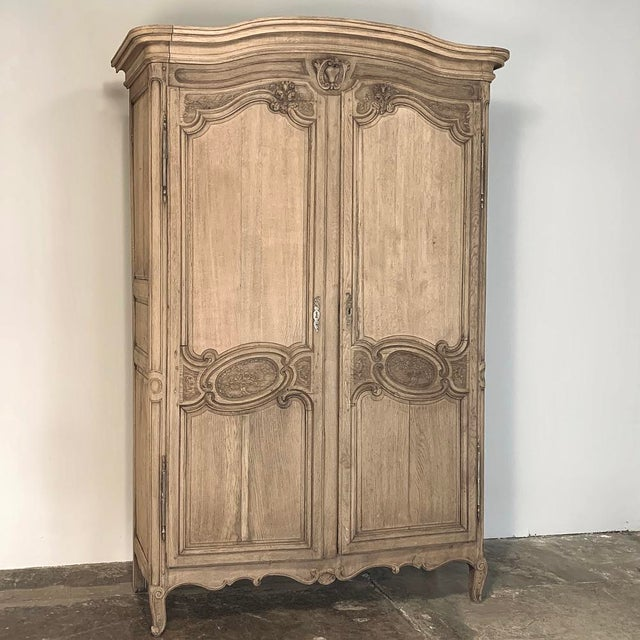 19th Century Country French Normandy Stripped Oak Armoire features the graceful lines that characterize the breed, with an...