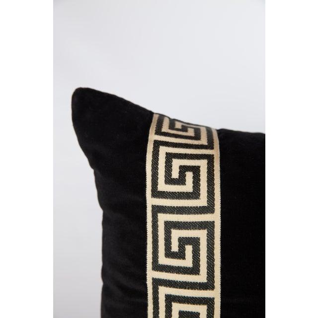 Pair of custom black velvet pillows with black-and-ivory Greek key tape on fronts. Solid black velvet backs. Knife-edge...