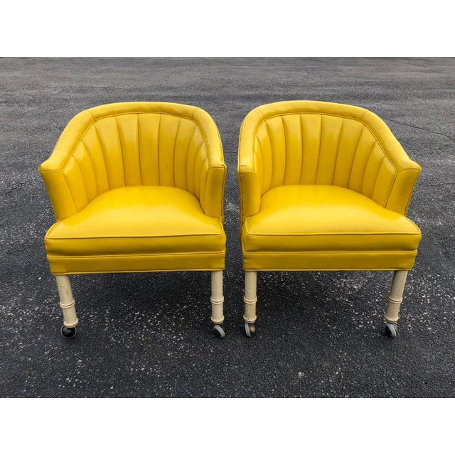 Pair of yellow channel back vinyl chairs on castors. Off-white faux bamboo legs with brass castors. Glam up that dressing...