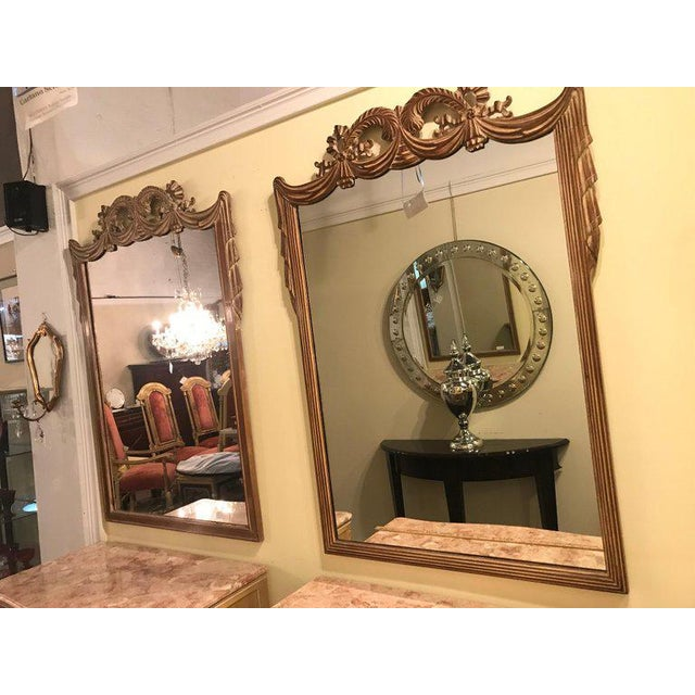 Pair of compatible Grosfed House Ribbon & Tassle form mirrors in the Hollywood Regency style. Each in a pickled wood.