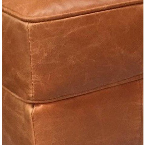 This is a plush ottoman in a Vienna Tan finish made from top grain full hide leather. This ottoman has flared dark stain...