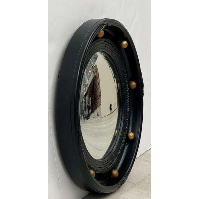 A fine English round or circular convex mirror featuring a Regency design of a molded, ebonized frame with gilt balls...