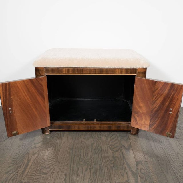 An Art Deco Machine Age storage bench in bookmatched walnut with original Bakelite and brass pulls. A newly upholstered...