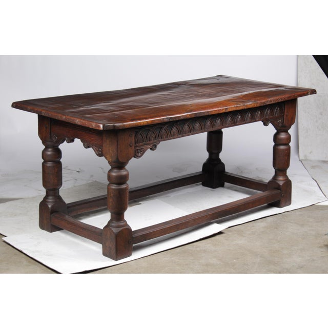 Antique French oak refectory table in the Jacobean-Style featuring sold dark oak construction, heavy slab top with...