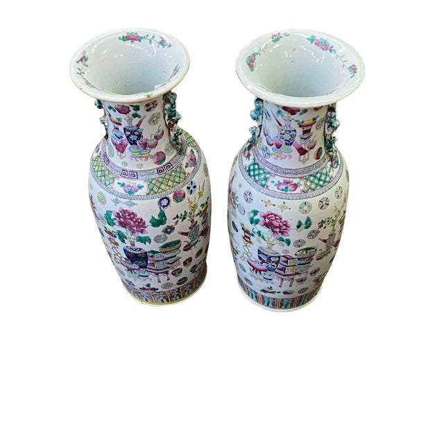 A tall pair of 19th century asian vases with wonderful colors and design depicting vases, tables and flowers.