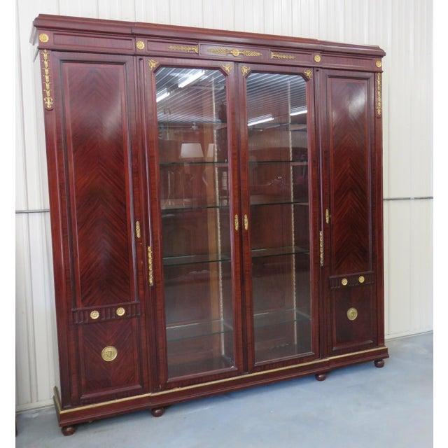 Regency style brass mounted 4 door breakfront. Center glass doors each contain 5 glass shelves. The doors on each side...