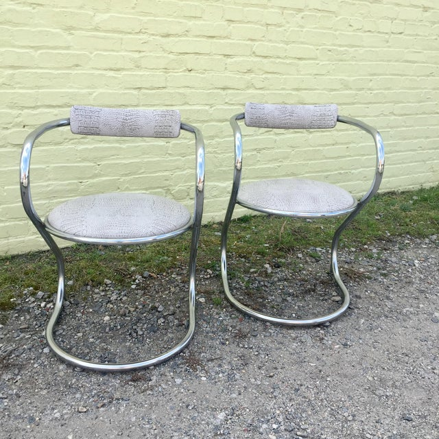 Beautiful modern pair of chrome cantilevered chairs styled after Thonet. Faux snake skin upholstery adds a unique touch....