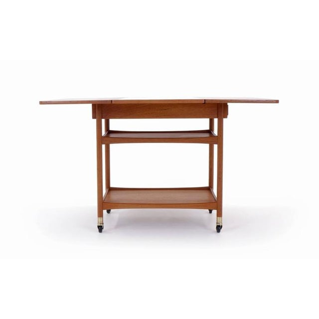 Versatile and unique Danish bar cart or serving cart with teak drop leaves and black laminate center surface. When you...