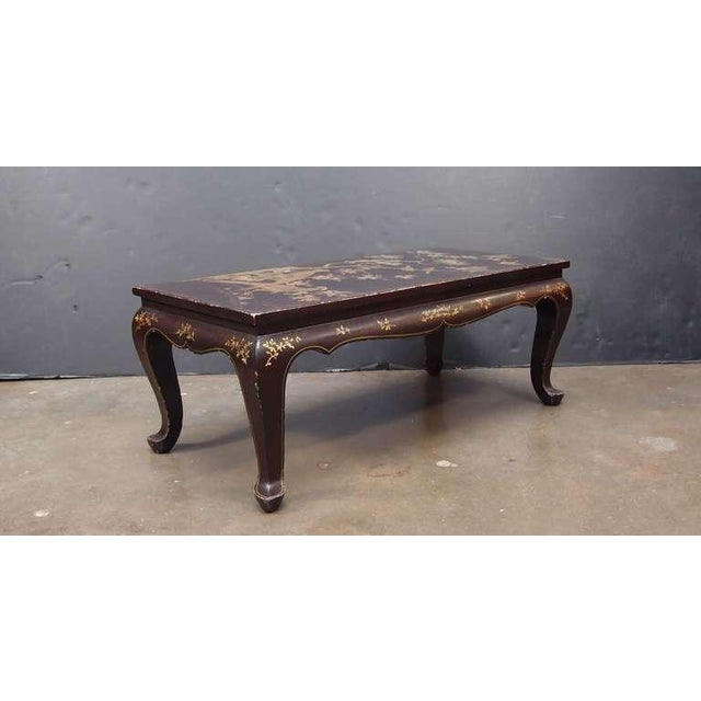 An attractive French chinoiserie brown lacquer coffee or cocktail table with gilt painted decoration. Set upon graceful...