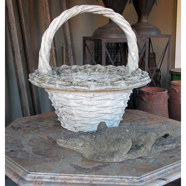 A boldly-scaled French faux basket-weave concrete jardiniere with arching handle; the tall braided handle joining a...