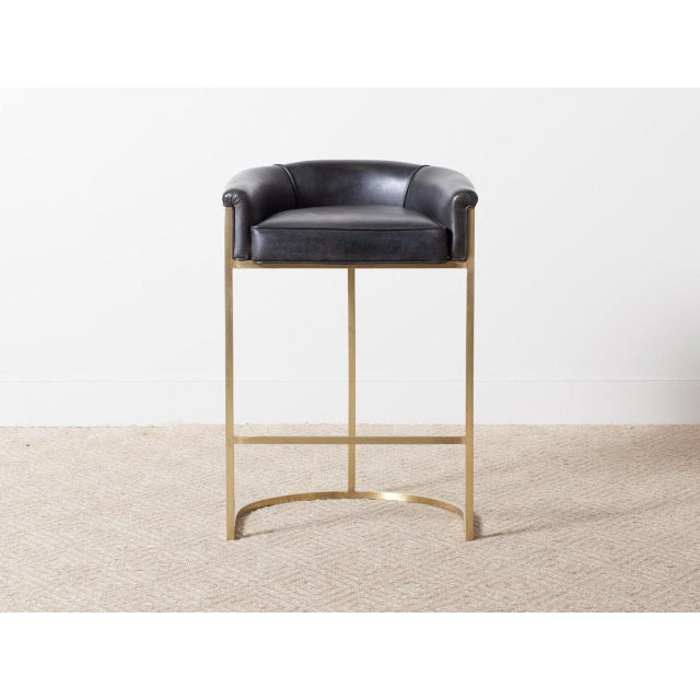 Brass framed barstool with black leather upholstered seat.