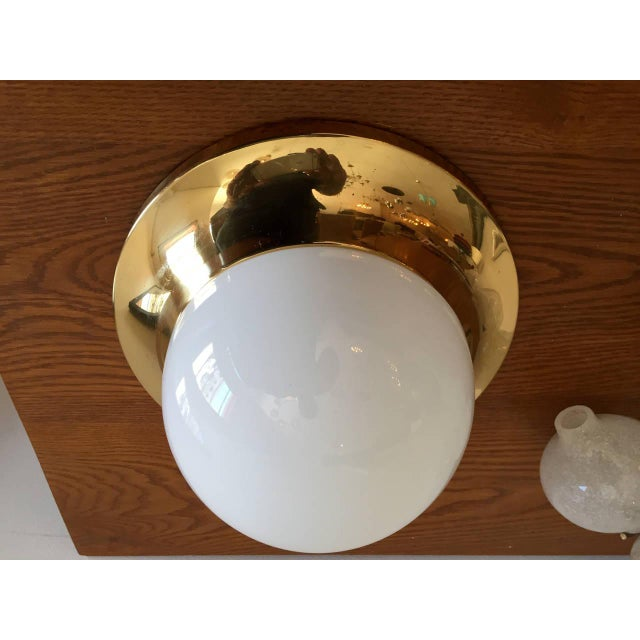 A 1960s Austrian Mid-Century flush ceiling light composed of a high polished golden brass fixture with a white opaline...