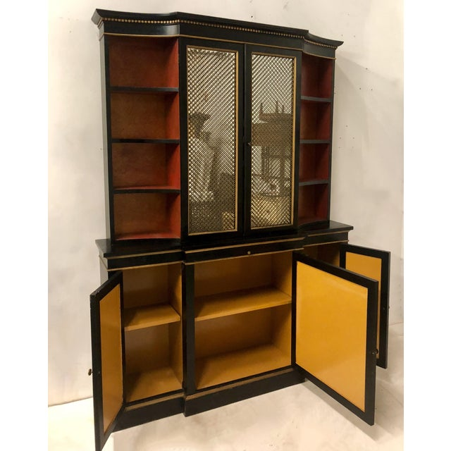 1960s Hollywood Regency cabinet with mirrored doors on the top that are under wire. The interior shelves are adjustable....