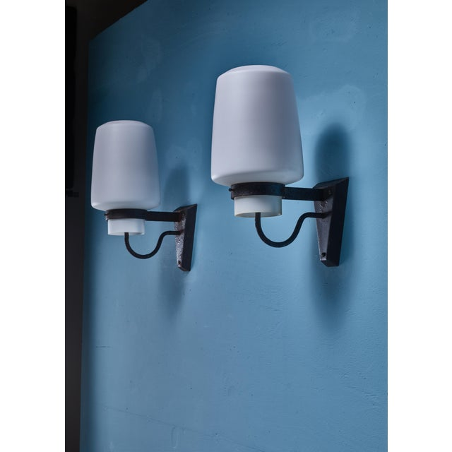 A pair of wall sconces by Georges Candilis. The lamps are made of a metal wall mount, holding an opaline glass diffuser...