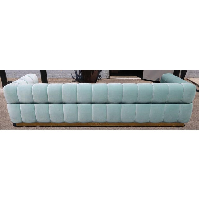 Custom tufted sofa with brass base, in aqua blue velvet. Can be made in different colors and fabrics or a different metal...
