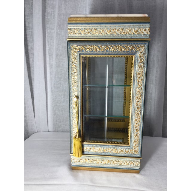 This Horchow ornately carved tabletop display case features an Italian marble top, gold accents, beveled glass door and...