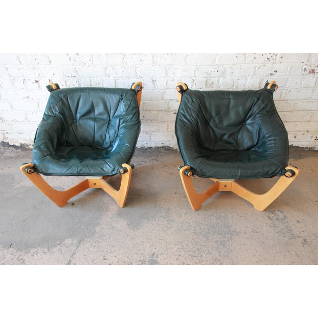 Offering a very nice pair of green leather 'Luna' chairs with teaks frames by Odd Knutsen. These extremely comfortable...