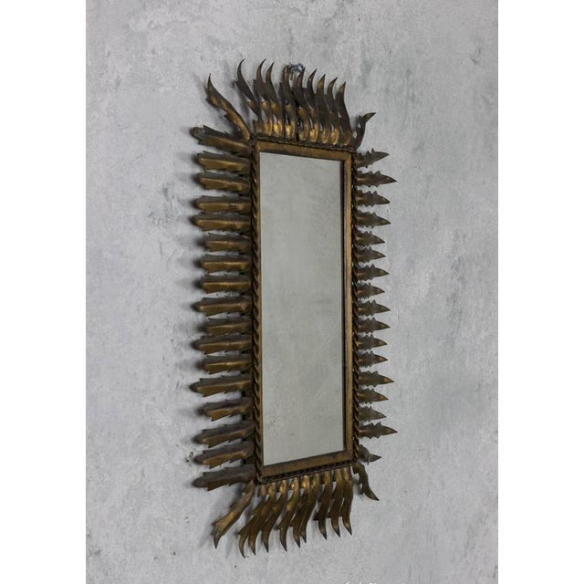Unusual gilt metal sunburst style mirror in a rectangular shape.