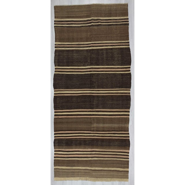 Handwoven striped natural kilim rug in black, brown, and white. In very good condition.