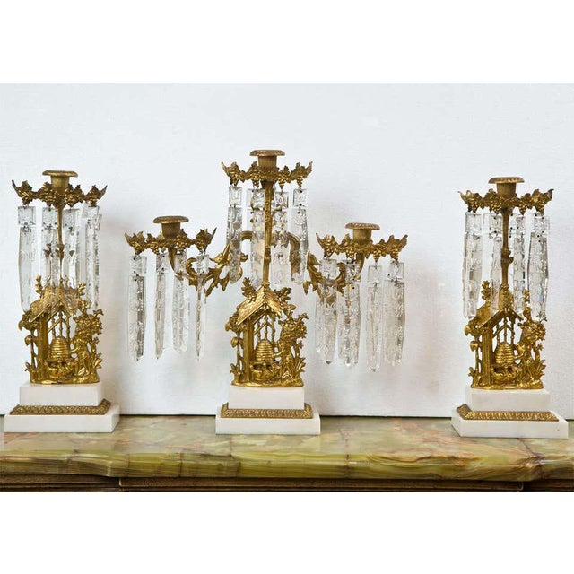 Set of three French Belle Époque style gilt-metal candelabras, the center piece has three arms, the other two each has one...