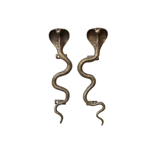 A pair of large brass cobra door handles or cabinet pulls. Hollywood Regency in style, with intricate carving throughout....