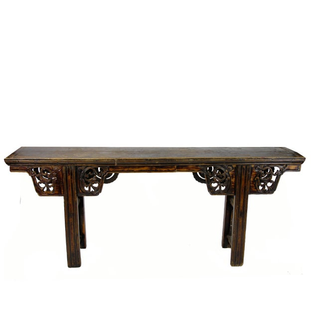This long narrow table has 4 nicely hand carved spandrels on both side of the table. The slightly splayed legs are joined...