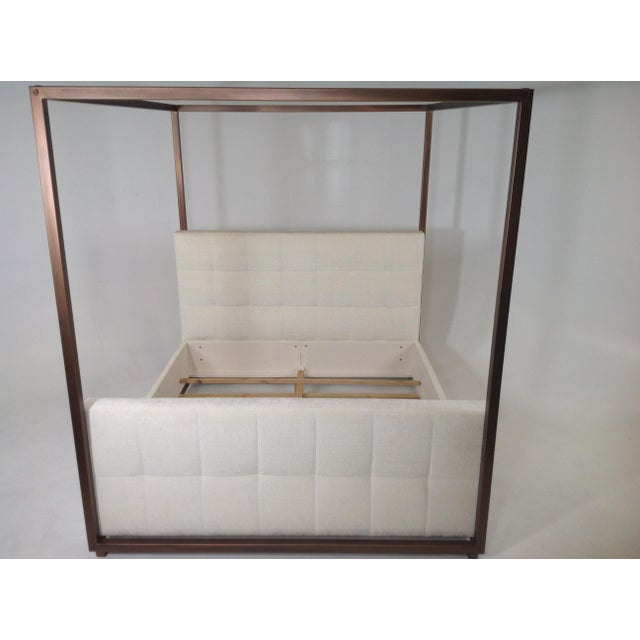 Stunning canopy Cal king bed. The bed is upholstered in a cream colored chenille. The frame is aluminum and has a copper...