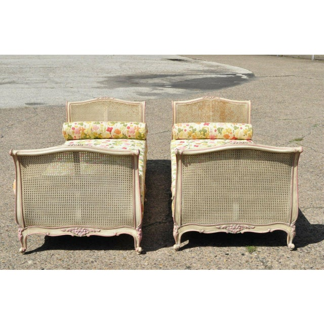 Pair of Antique French Louis XV Style Pink & Cream Painted Carved Wood & Cane Daybeds. Item features double cane foot and...